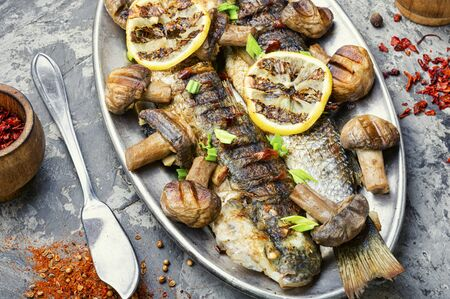 Baked whole pelengas fish with mushrooms and lemon.Sea food.Grilled fish with mushrooms.