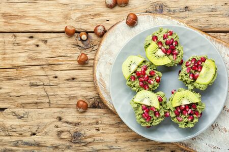 Diet avocado cupcakes garnished with kiwi and pomegranate.Cupcakes on wooden background