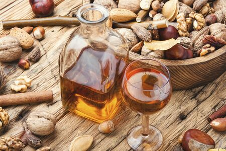Shot glass with aromatic alcohol from nuts.Nut liquor.Tincture on nuts. Reklamní fotografie