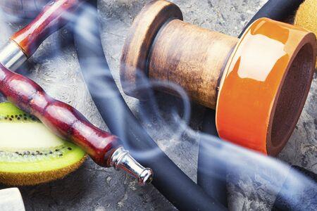 Turkish tobacco hookah on kiwi.Fragrant oriental hookah.Details of a smoking hookah.Fruit tobacco for hookah.