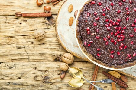 Tasty homemade chocolate cake with pomegranate and nut.