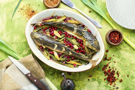 Pelengas baked with vegetables and pomegranate.Tasty baked whole fish