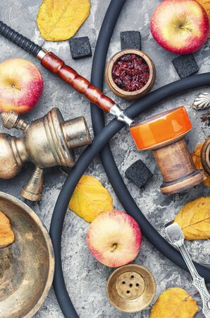 Oriental smoking shisha.Hookah bowl and tobacco.Details of Turkish nargile.Kalian tobacco with apple aroma and quince. Stock Photo