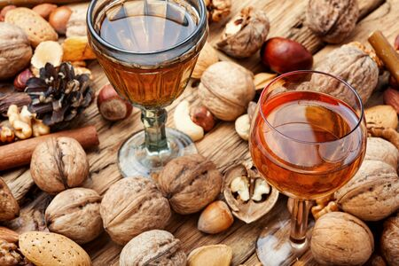 Shot glass with aromatic alcohol from nuts.Nut liquor.Tincture on nuts.Nocino Stock Photo