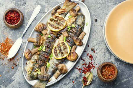 Roasted pelengas fish with mushrooms and lemon.Sea food.Grilled fish with champignon Stock Photo