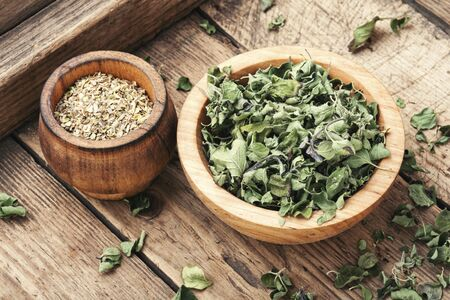 Bowl of dried oregano leaves on wooden background