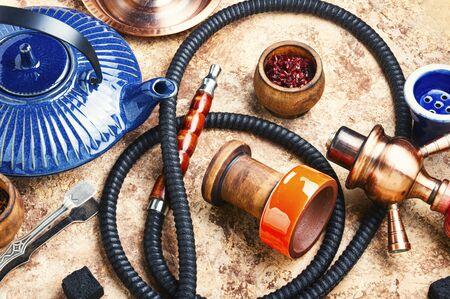 Details of tobacco hookah and teapot with tea.Egyptian smoking shisha and teakettle Stock Photo