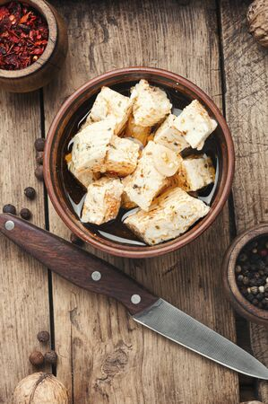 Feta cheese with spice and garlic on old wooden