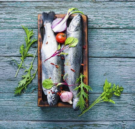 Fresh whole raw trout on a kitchen board.Fresh fish with vegetables and seasonings. Stok Fotoğraf
