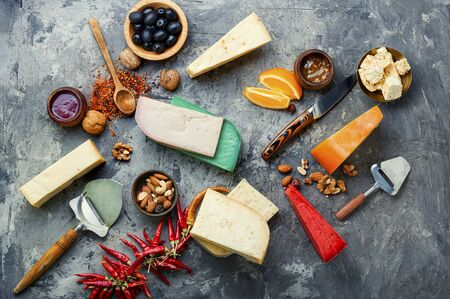 Large assortment of international cheese on slate background.Cheese variety