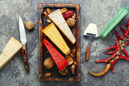 Wooden kitchen board with different kinds of delicious cheese on table Stok Fotoğraf