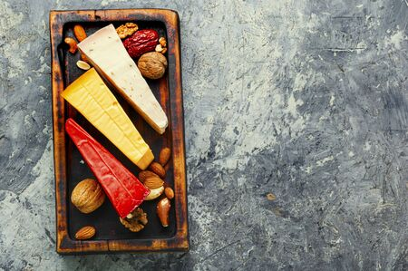 Kitchen board with different kinds of delicious cheese on table.Three slices of cheese on a wooden kitchen board