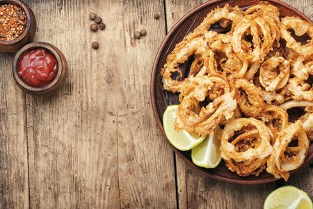 Fried squid rings breaded with lime on wooden background Stok Fotoğraf