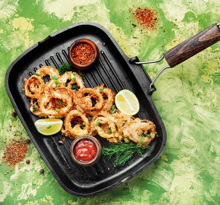 Fried calamari rings with sauce.Fast food.Fried rings of squid in the frying pan