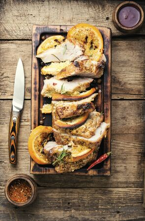 Sliced pork meat stuffed with oranges.Roasted meat on the kitchen board.