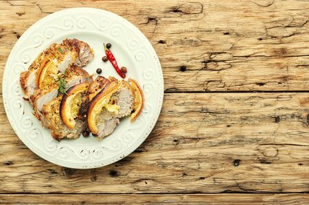 Baked pork meat stuffed with orange and seasonings.Grilled pork with orange fruit Stok Fotoğraf