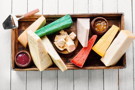 Various kind of cheese served in wooden box.Various types of cheese on white wooden table