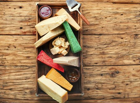 Various kind of cheese served in wooden box.Various types of cheese on rustic wooden table