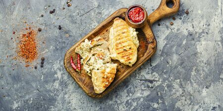 Roasted chicken breast stuffed with cheese, seasonings and sauce on the kitchen board