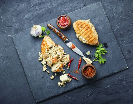 Baked chicken breast stuffed with cheese feta.Whole and sliced chicken breast