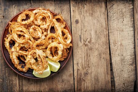 Crunchy deep fried squid rings in batter on wooden background