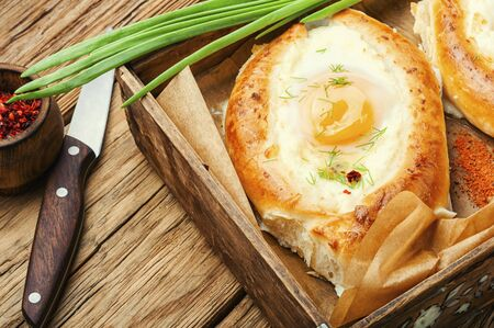 Khachapuri Georgian national flour product, a pie stuffed with cheese and eggs Фото со стока
