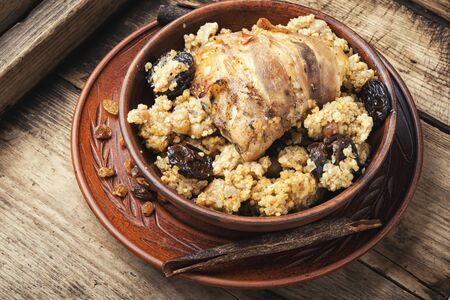 Millet porridge with chicken in bacon, with spices and dried fruits.Rustic food on vintage wooden background.