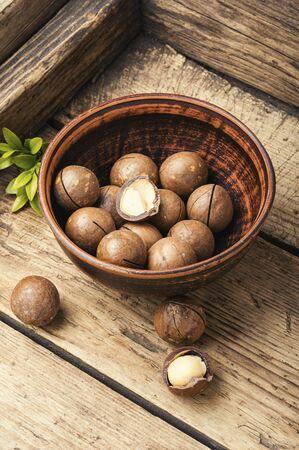 Macadamia nut on wooden table.Heap of macadamia nuts