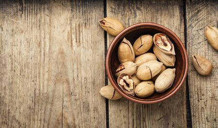 Pecan nuts in bowl on a rustic wooden table
