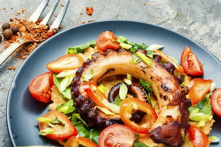 Grilled octopus salad with tomato, spinach, pepper and lemon
