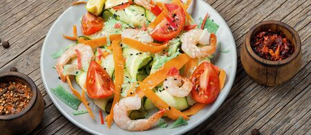 Diet salad with tomato, cucumber and shrimp.