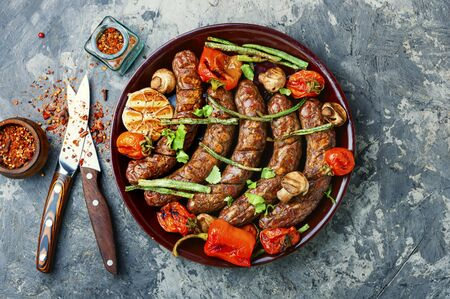 Grilled sausage with mushrooms and tomatoes.Fried bbq sausages with vegetables Stock fotó