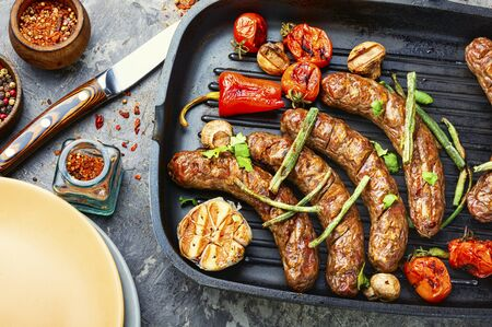 Grilled sausage with mushrooms and tomatoes in grill pan