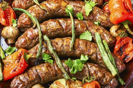 Delicious german sausages with grilled mushrooms and tomatoes.BBQ with sausage Stock fotó