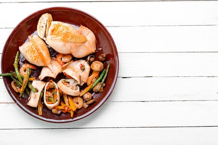 Squid stuffed with mushrooms, carrots and peppers.Baked seafood with vegetables Stock fotó
