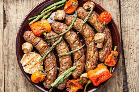 Grilled sausage with mushrooms and tomato.Fried sausages on wooden table