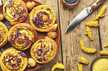 Baked buns with potatoes and mushrooms on wooden table.Turmeric dough.