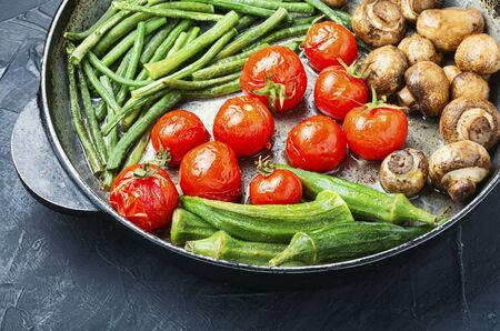 Mushrooms, tomatoes, beans and vigna cooked on grill.Grilled vegetables in iron grilling pan