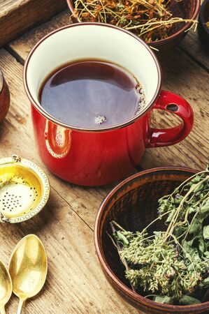 Cup with tea from medicinal herbs on a wooden background