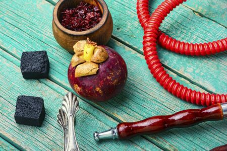 Asian smoking hookah with shisha tobacco with mangosteen flavor. Fruit nargile tobacco on wooden background.