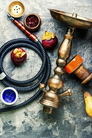 Shisha with fruit tobacco.Hookah with the aroma of tropical mangosteen fruit. Stock Photo