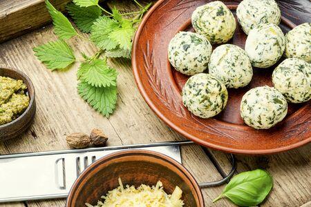 Malfatti with nettles on old wooden table.Italian food
