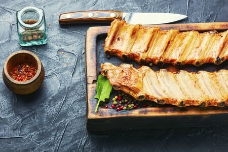 Smoked pork ribs on a wooden kitchen board.