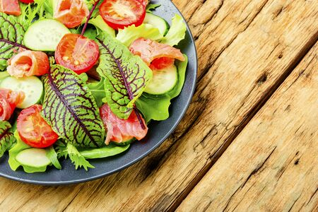 Salad with salted salmon,vegetables and herbs in plate on a wooden old table.