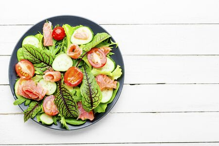 Appetizing salad with salmon, vegetables and herbs.