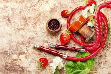 Oriental smoking hookah with strawberry tobacco. Berry hookah tobacco. Foto de archivo