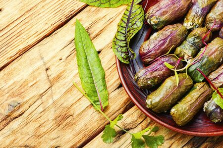 Traditional oriental dolma in grape leaves on rustic wooden table Imagens