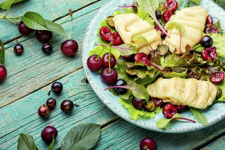 Summer salad of leaf lettuce, fried halumi cheese and cherry berries