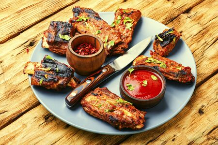 Fried beef ribs with tomato sauce on a old wooden table 스톡 콘텐츠