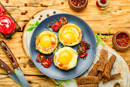 Fried eggs with tomatoes and bread in plate on rustic wooden table